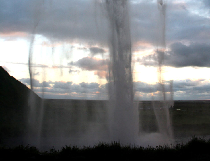 A scenic photograph from behind Seljalandsfoss in Iceland