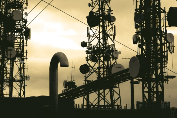 An altered photograph of communication towers with yellow sky and dark green towers