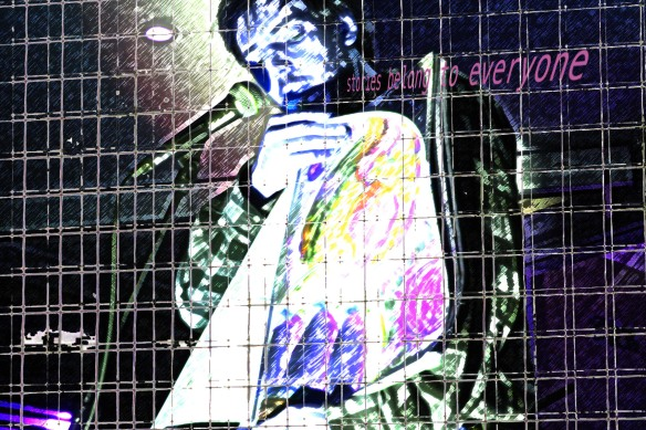 A doctored photograph of musician Jeffrey Lewis showing some of his graphic art from behind bars