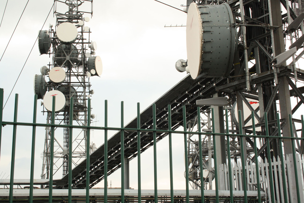 An image of a communications tower behind a fence.