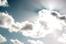A dynamic photograph of an airplane flying through crepuscular rays
