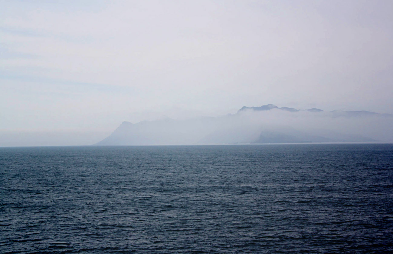 A photograph of an island emerging from the clouds with aa seascape in between