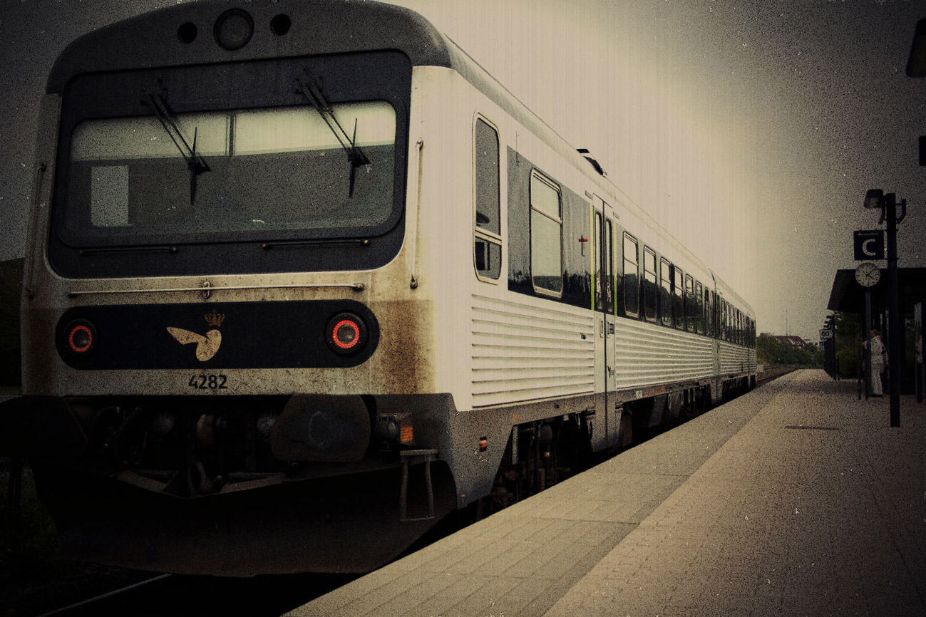 A photograph of a train pulled in at Aalborg station, edited with a vignette to look weathered
