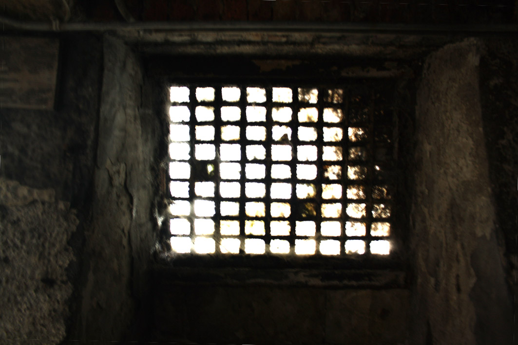 A photograph of a dark grill with light coming through, representing a prison