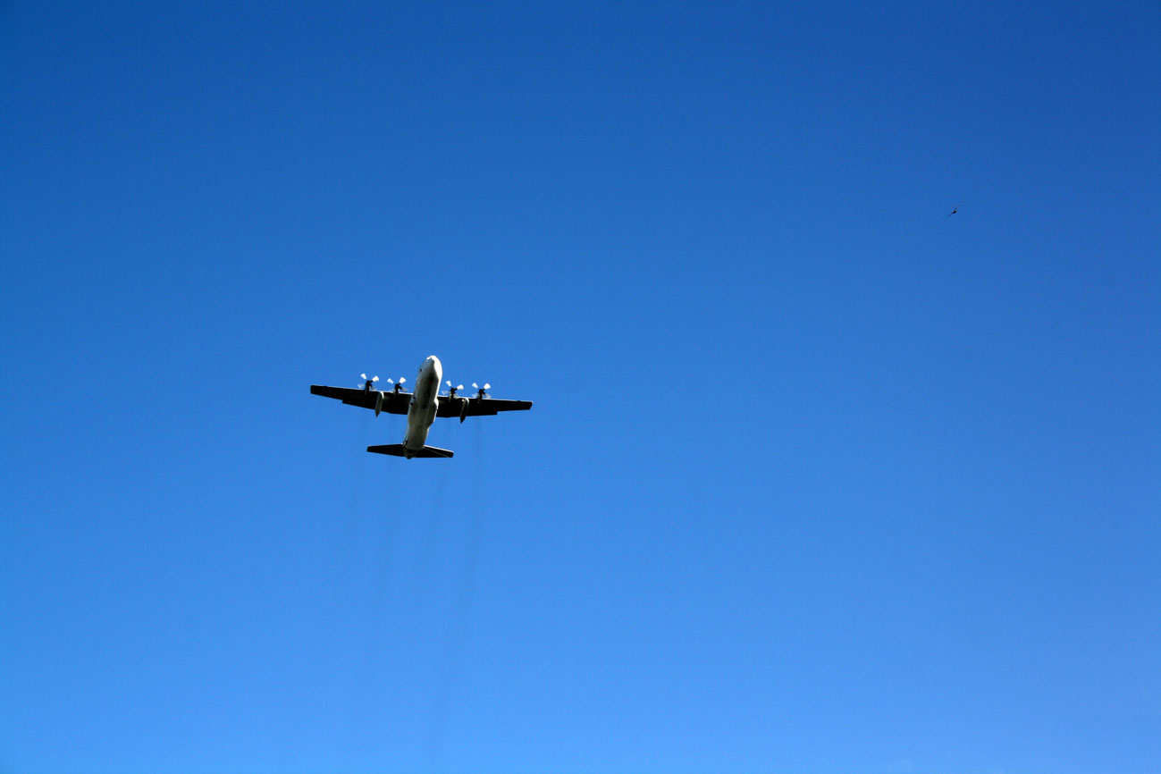 A photograph of an aeroplane from beneath in a very blue sky