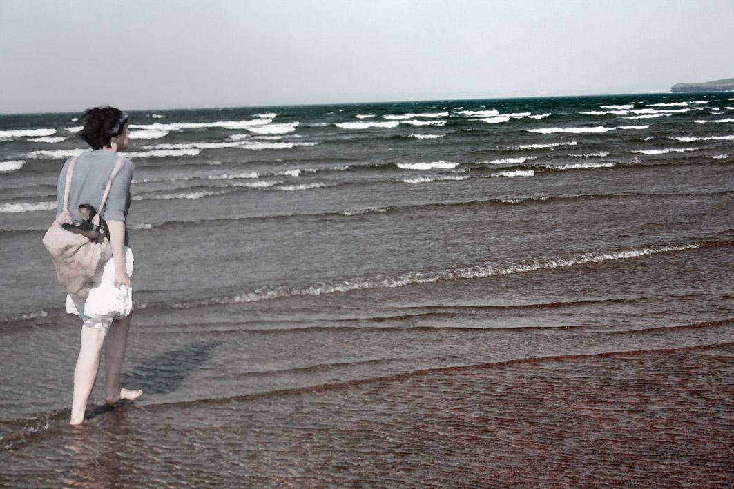 An edited photograph of a girl walking toward the horizon line of an ocean