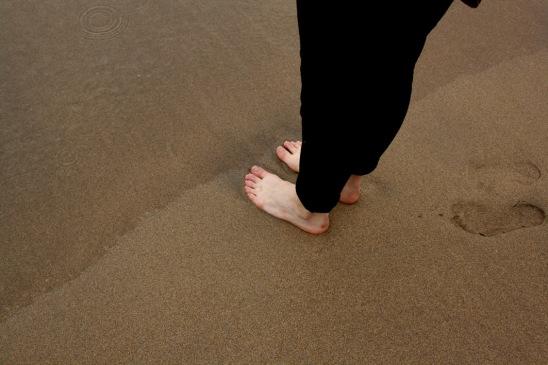 A photograph of feet on a sandy beach