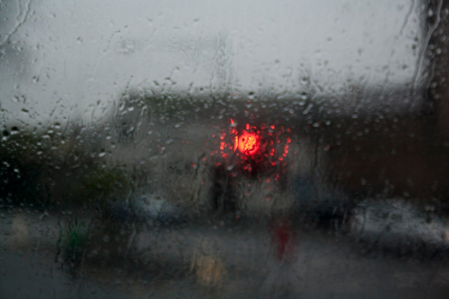 A photograph of rain falling down a window with a red light distorted in the blur of the exterior